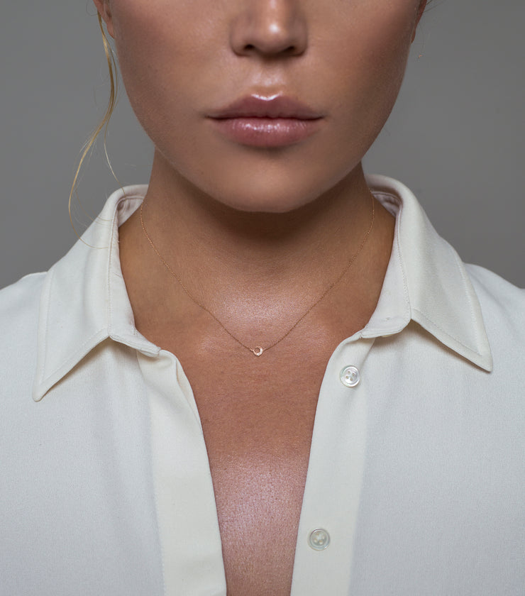 Woman wearing the Oliver Heemeyer Moon diamond pendant designed in 18k rose gold, crafted with three small and sparkling diamonds. A delightful piece of jewelry wearable on any occasion.