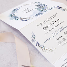 Winter wedding invites featuring pine trees and reindeer
