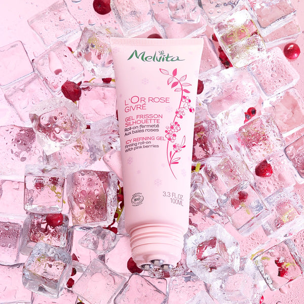Melvita Slimming Body Care L'or Rose Icy Refining Gel with cap open and placed among ice cubes and berries