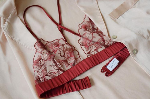 Fleur of England red luxury lingerie embroidered boudoir bra placed on a silk blush pyjama shirt