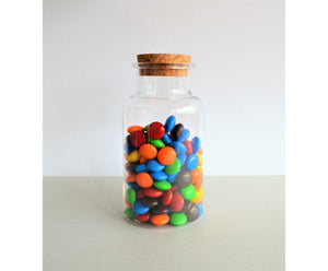 Chocolate M&Ms in a candy jar with a cork lid