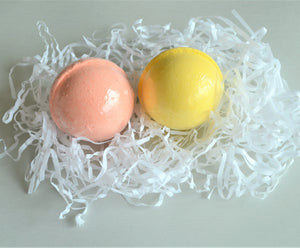 2 bath bombs – pink peach and yellow pina colada, in white shredded tissue paper