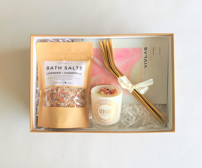 The Swirl Box Pink n Gold gift box for her with lavender chamomile bath salts, bloom candle, gold stainless steel straws and lotus face sheet mask