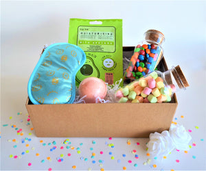 The Swirl Box Gift Hamper for Her with eye mask, face sheet mask, bath bomb, and marshmallows and M&Ms in candy jars, with white roses and confetti