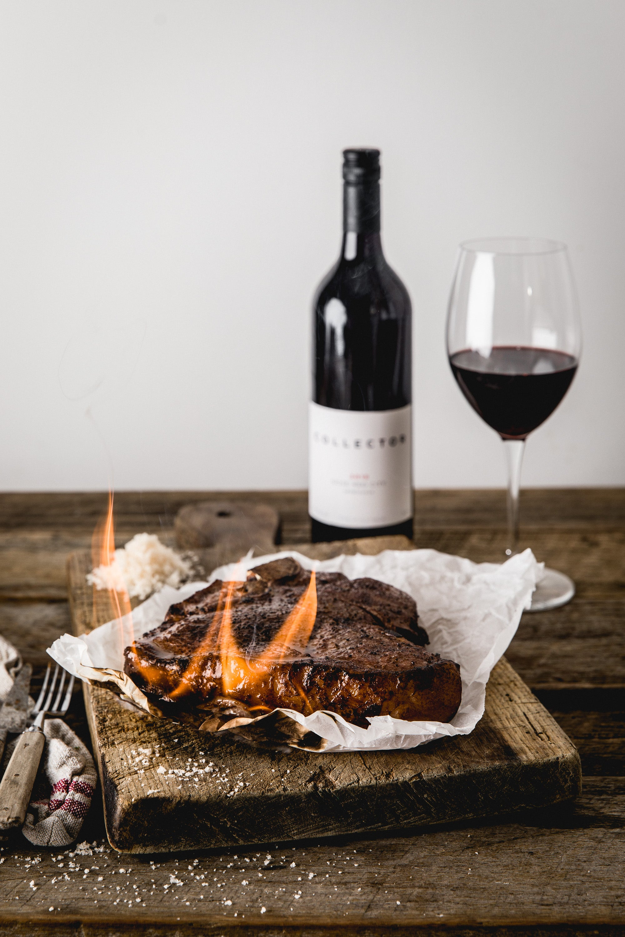 A T-bone steak, grilled and with flames still licking its sides, rests on a rustic wooden board. A bottle and glass of Collector Wines Rose Red City Sangiovese sits in the background.
