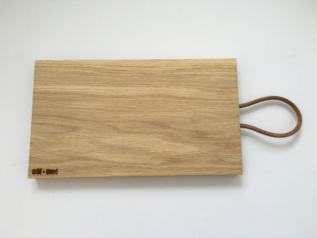 Oak chopping or serving board with leather strap by Wild+Wood