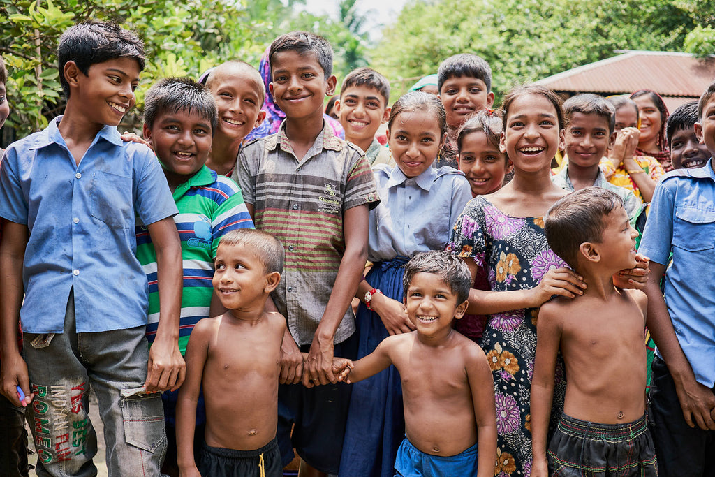 Group of children from Bangladesh holding hands and smiling
