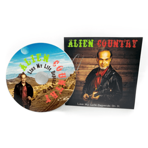 A photo of a CD and it's sleeve. The Sleeve has a picture of Liam Marcus holding an electric guitar. The CD art is a picture of Liam Marcus standing on a scenic  highway with mountains in the background. Scifi country rock