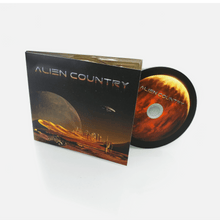 Load image into Gallery viewer, Alien Country Album cover - a red planet with sand dunes futuristic city on the horizon with alien moon and flying saucer high above. An antique pickup truck from Earth is driving along a dirt road which leads to the city.
