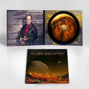 Alien Country Album cover - a red planet with sand dunes futuristic city on the horizon with alien moon and flying saucer high above. An antique pickup truck from Earth is driving along a dirt road which leads to the city.