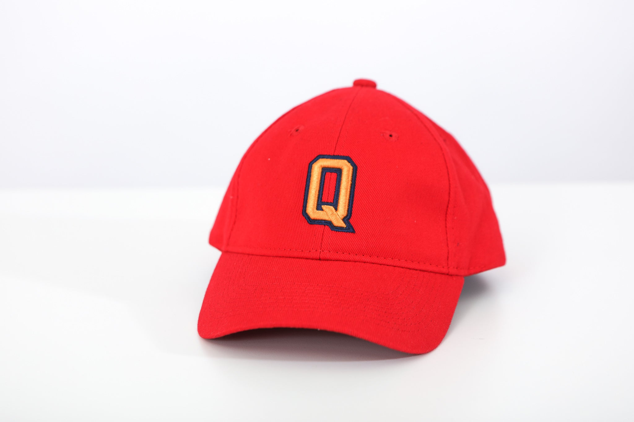 Front image of red hat with yellow Q logo