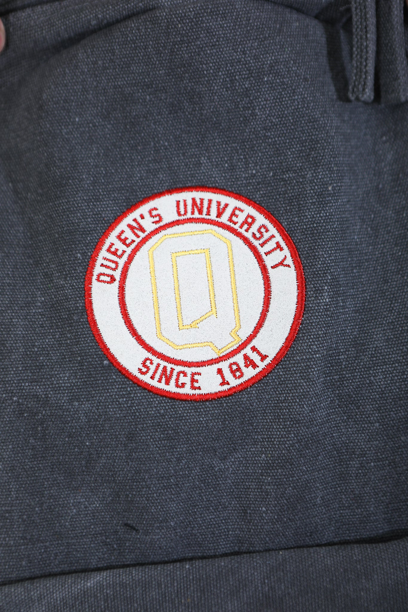 Close up of grey backpack with circular Queens logo