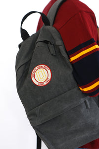 Grey backpack with circular Queens logo
