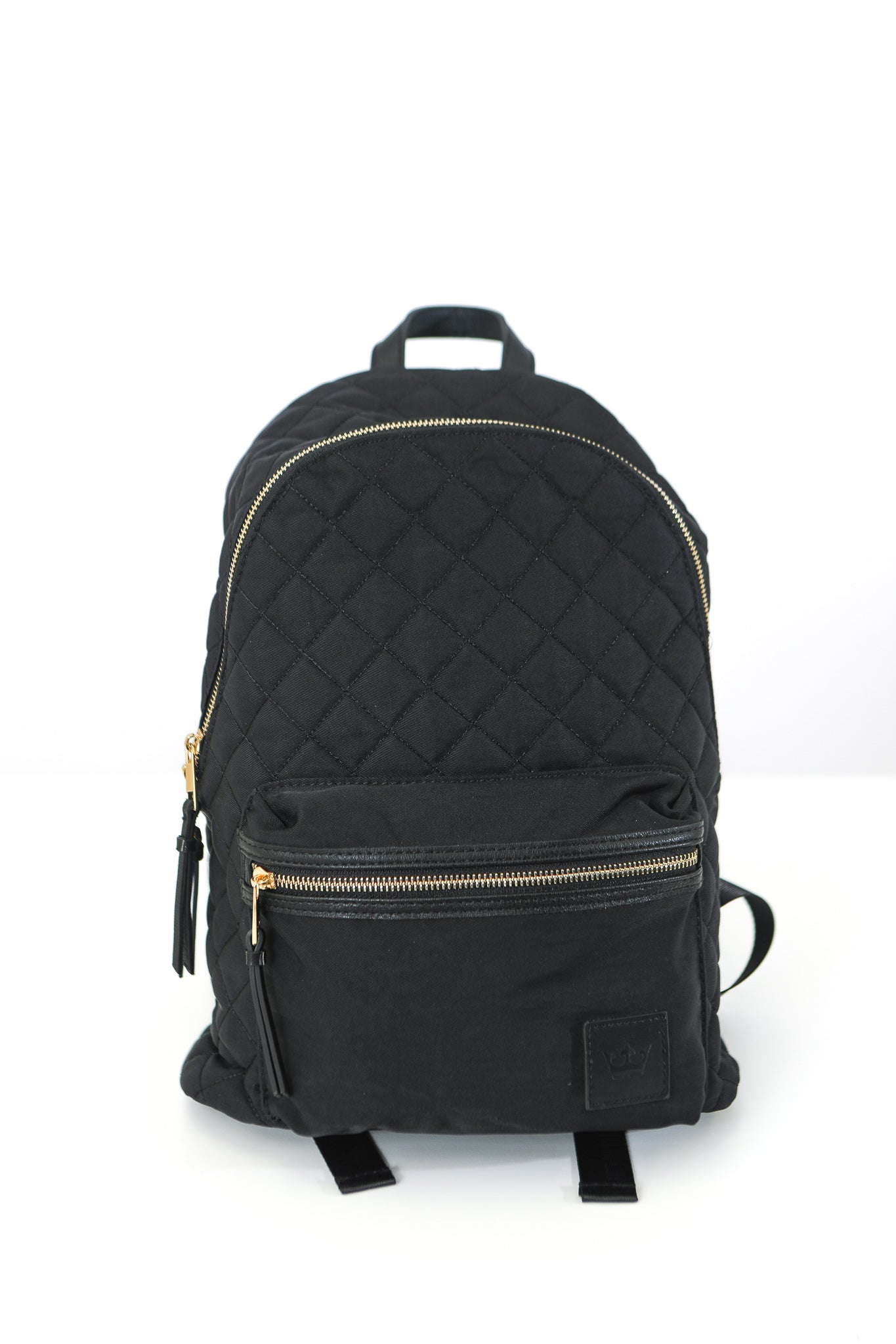 Back of black backpack with quilted pattern and gold zippers