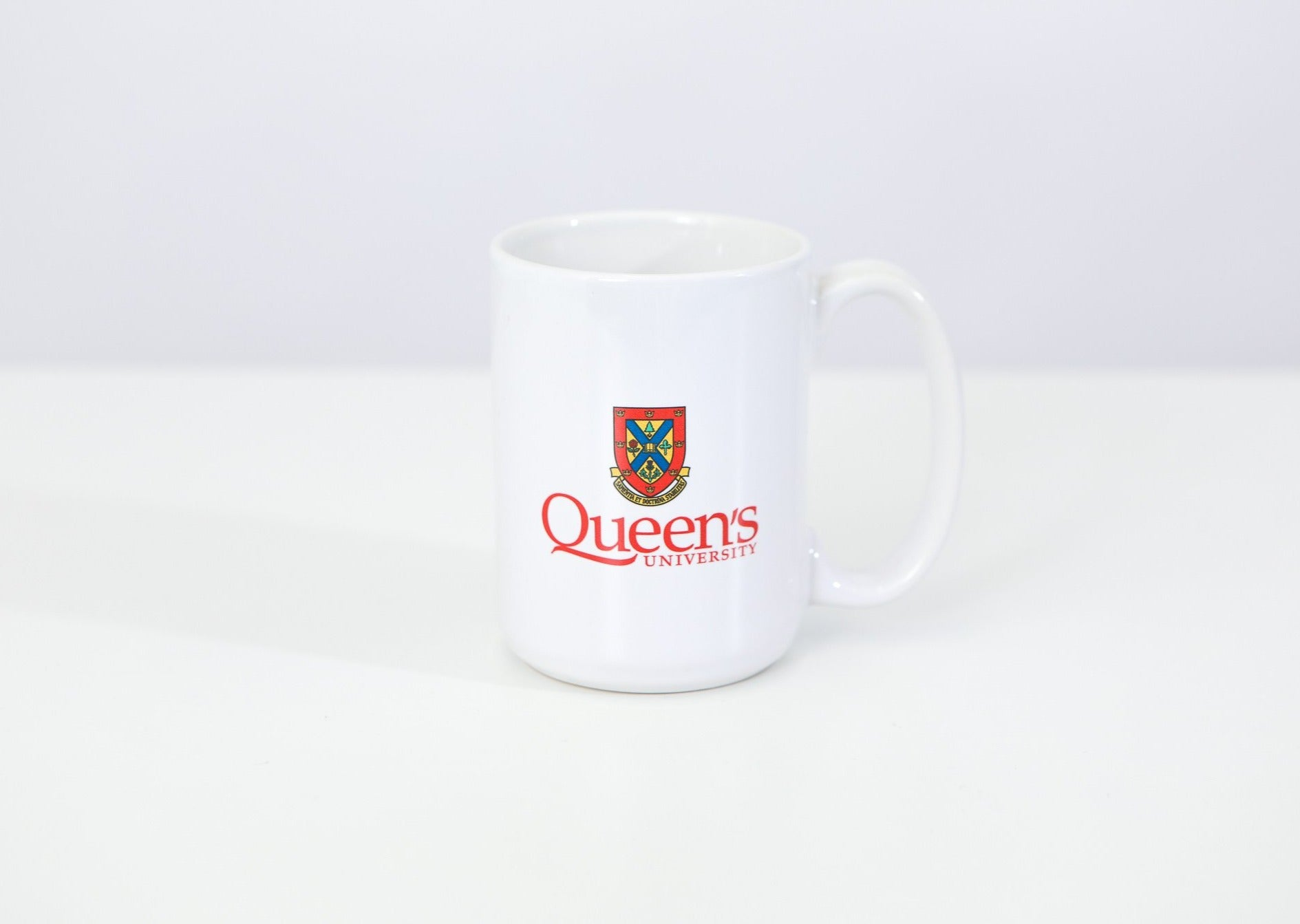 White ceramic coffee mug with the Queen's crest on it