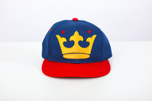 Front of blue hat with a red brim and large embroidered yellow crown