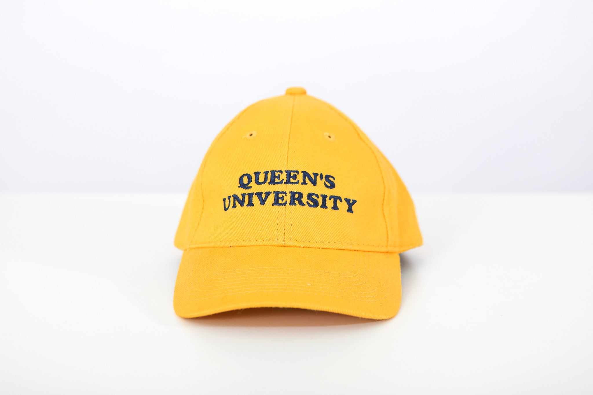 Yellow baseball cap with Queen's University embroidered on the front in Navy