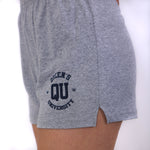 Close up of grey jersey knit cotton shorts with a stretchy waistband and a navy QU on the front of the thigh