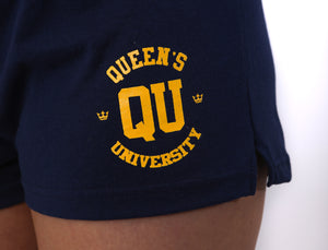 Close up of navy jersey knit cotton shorts with a stretchy waistband and a gold QU on the front of the thigh