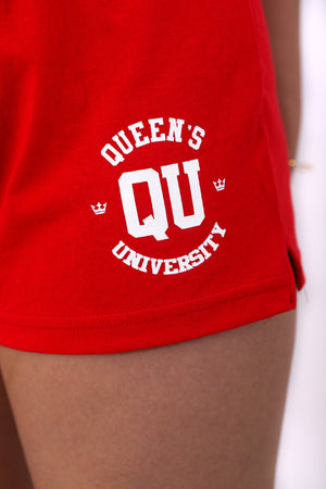 Close up of Red jersey knit cotton shorts with a stretchy waistband and a white QU on the front of the thigh