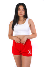 Red jersey knit cotton shorts with a stretchy waistband and a white QU on the front of the thigh