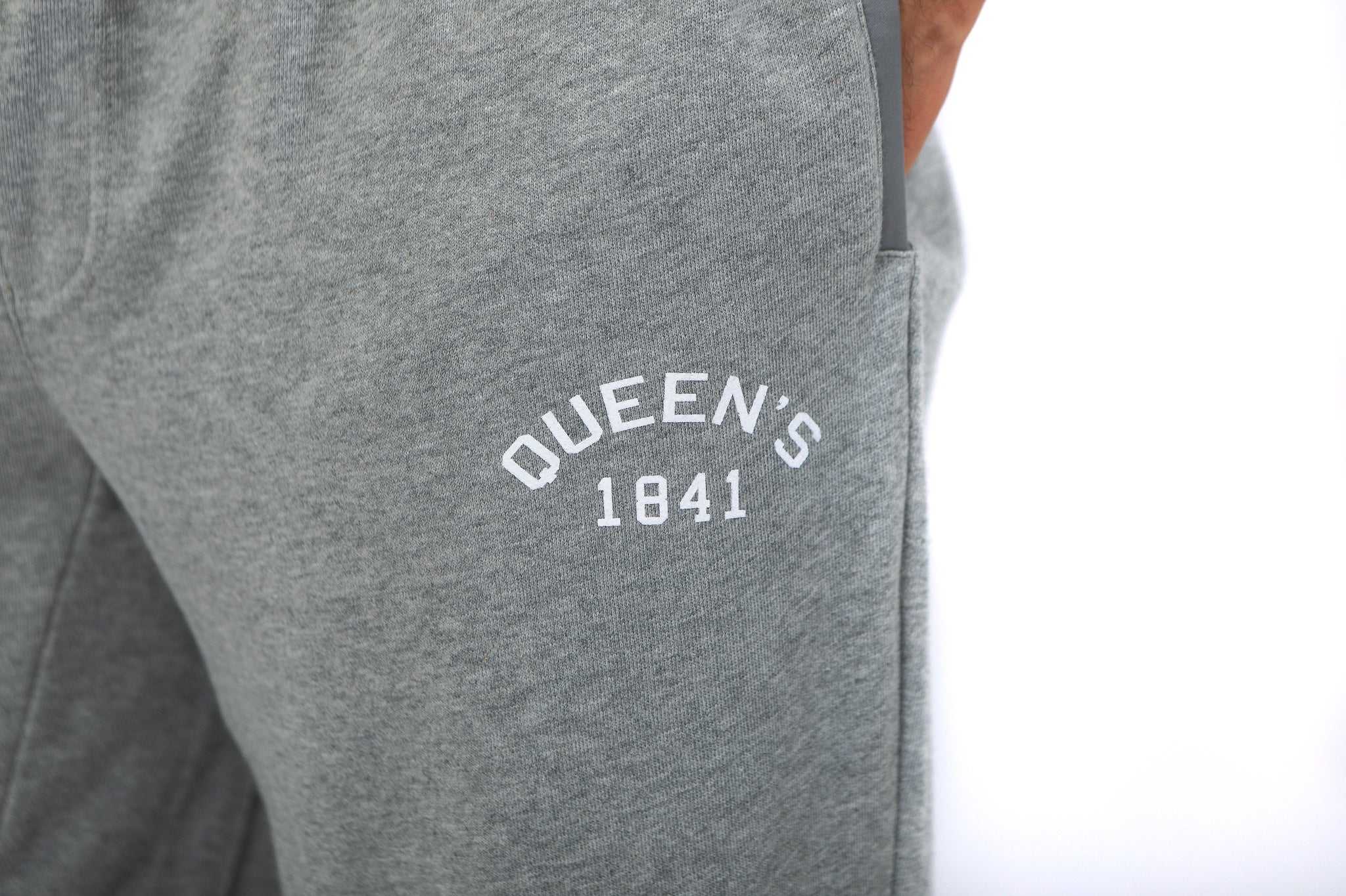 Close up of white Queen's logo on grey sweatpants