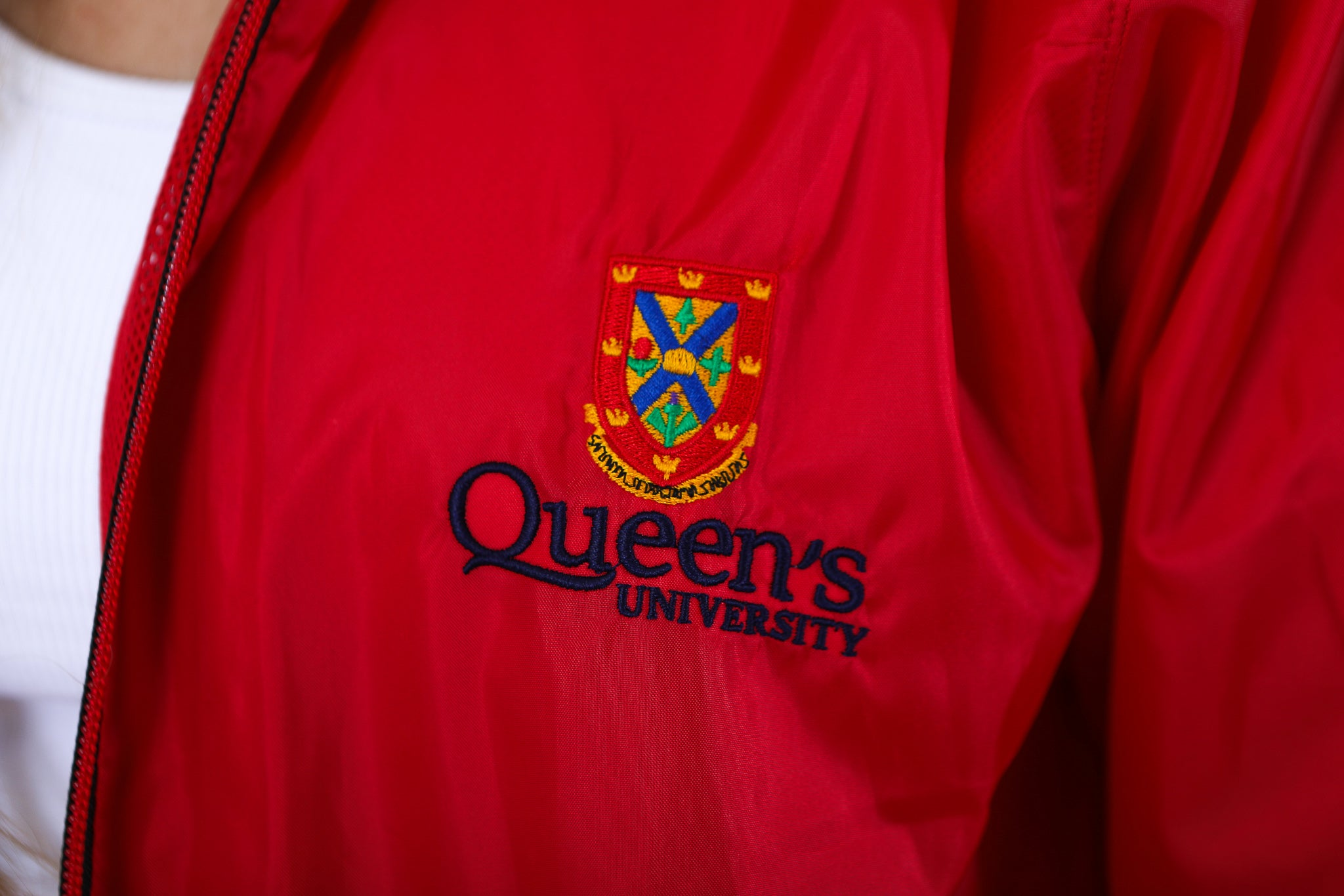 Close up of red zip up rain jacket with red Queen's crest logo
