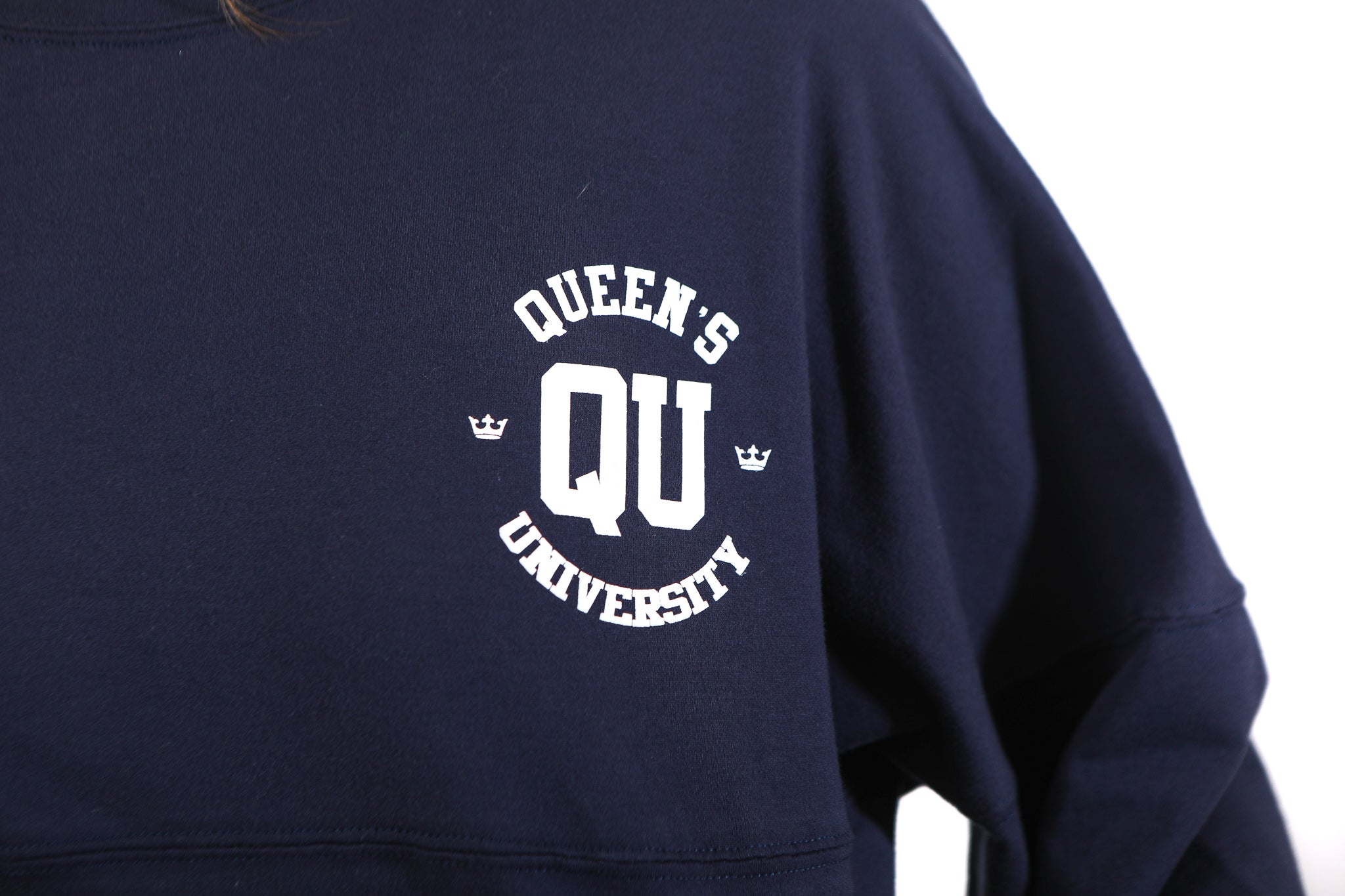 Close up of QU logo in white on blue shirt