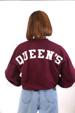 Back of red shirt with Queen's written across in white