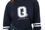 Close up of navy longsleeve with stripes on the sleeves and a large Q in the front