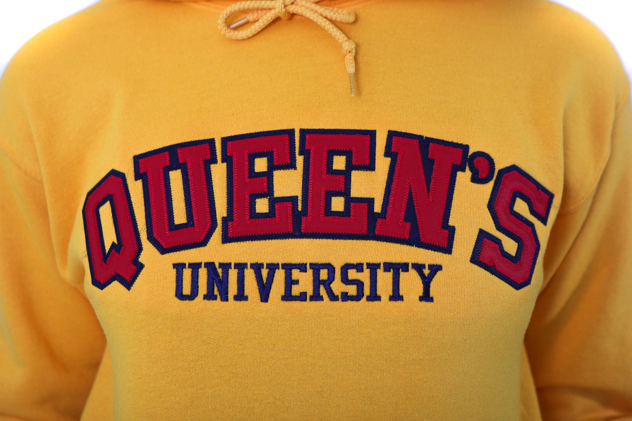 Close up of red Queen's logo on yellow sweater
