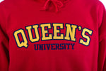Close up of yellow Queen's logo on red sweater