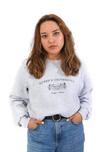 model wearing a grey crewneck sweatshirt with an illustration of ontario hall