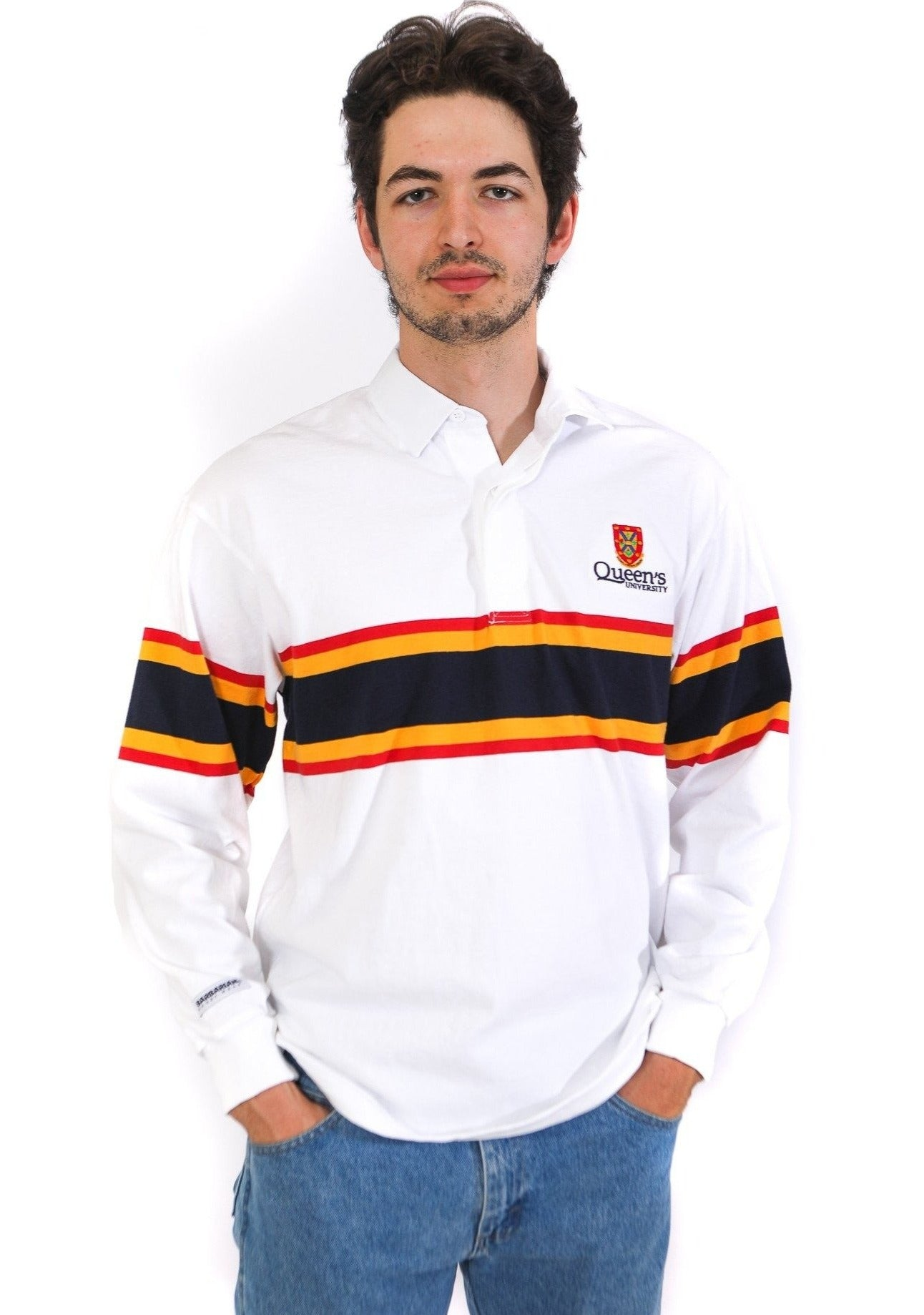 Model in a white rugby shirt with thin red and yellow stripes and a thick navy stripe across chest