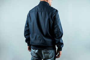 Man wearing a navy sports jacket from behind