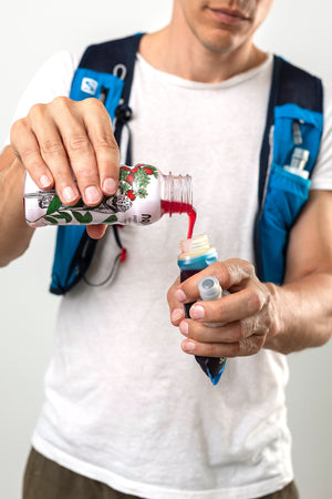 Man pouring Nosht running energy gel into reusable running flask