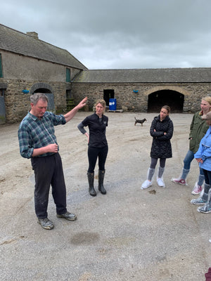 Group with farmer, in an old farmyard. Dog in the background