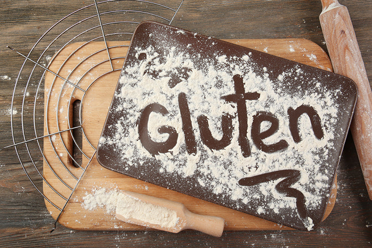 The word gluten written by finger in powder on a cutting board.