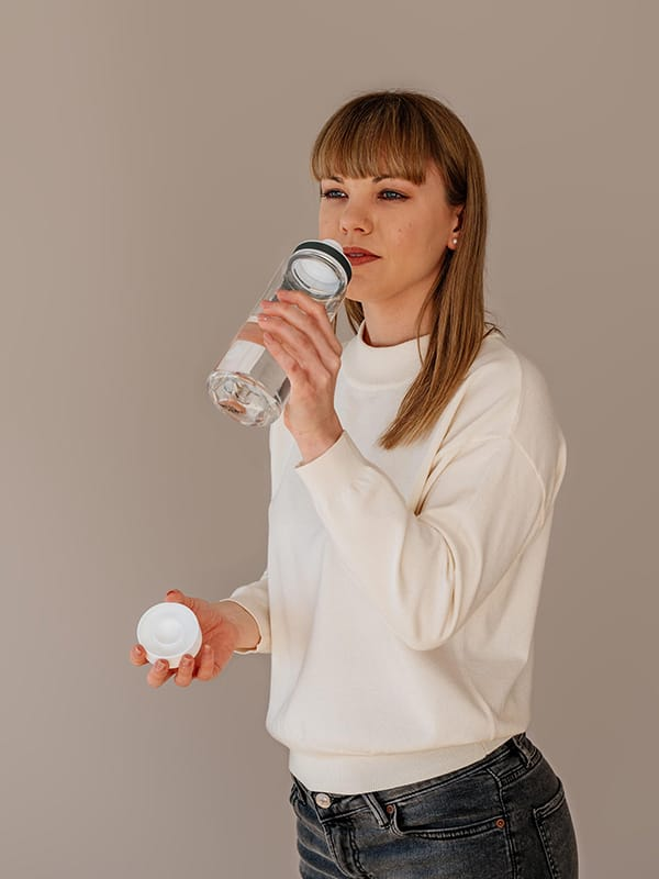 EQUA BPA FREE water bottle, Plain White, young woman drinking from the water bottle, minimalistic design, no motif, white color