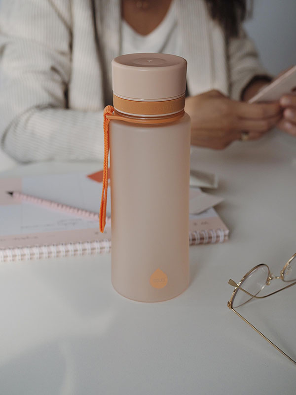 EQUA BPA FREE water bottle, Sunrise, water bottle on the office table, woman is working in the background, minimalistic design, no motif, peach color