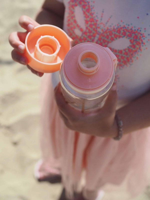 EQUA BPA FREE water bottle, Playground, open bottle held by a little girl shows lid and mouthpiece, pink color