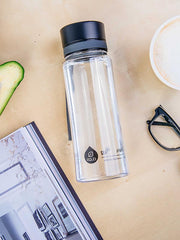 EQUA BPA FREE water bottle, Plain Black, on the dinning table, together with coffee, reading glasses and a magazine, minimalistic design, no motif, black