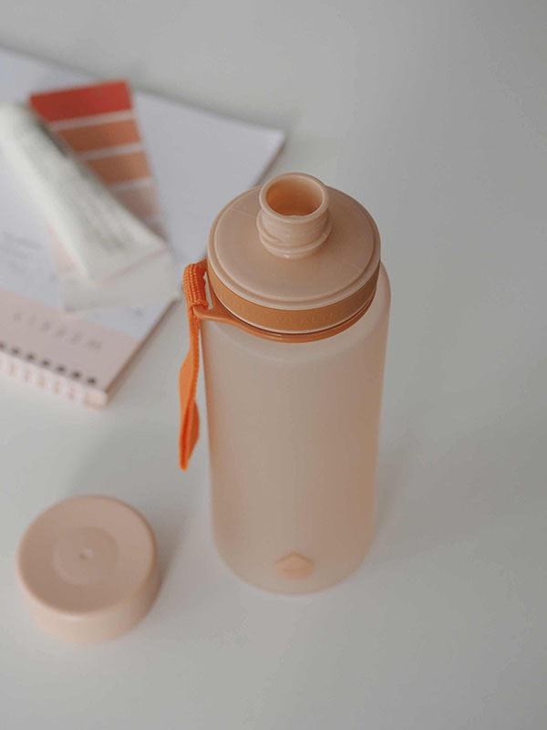 EQUA BPA FREE water bottle, Sunrise, close up of the water bottle on the office table, minimalistic design, no motif, peach color