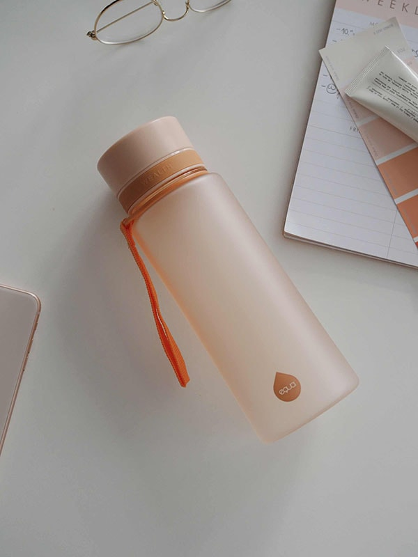 EQUA BPA FREE water bottle, Sunrise, water bottle on the office table, minimalistic design, no motif, peach color