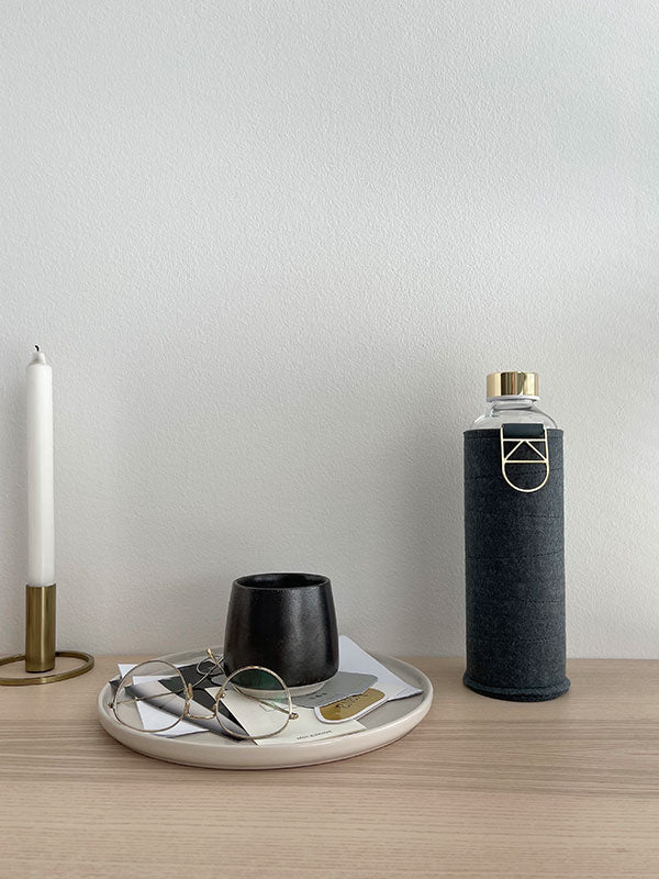 EQUA Blueberry Pie bottle with blue felt cover and gold details as handle and lid. Next to minimal design candle, cup and glasses