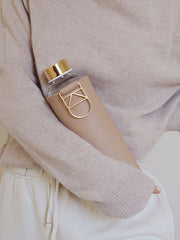 Beige cover with gold hanger and gold lid glass water bottle by EQUA