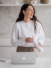 Lady holding Stainless steel smart water bottle Snow white standing next to the laptop. Glow reminder for hydration is active. Gold details on the water bottle lid. Glow reminding her to take a sip of water.