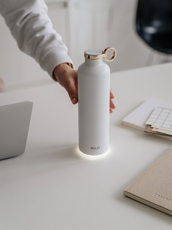 EQUA Smart Water Bottle Snow White made from Stainless Steel in White Colour and Gold Lid and Ring detail in the center of the image with hand reaching out to take it to make a sip.