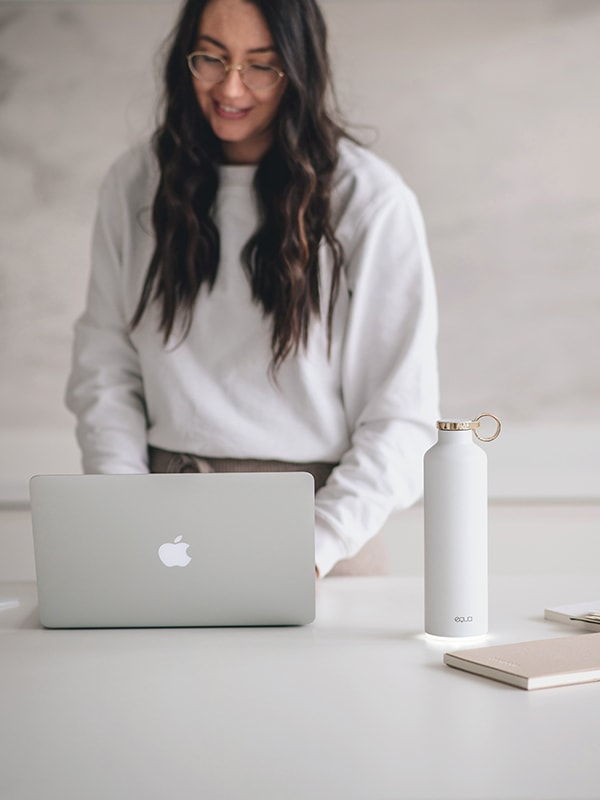 Smart Water Bottle EQUA in White Colour on the right bottom part of the image. With lady in the background working on her lap top. Glow reminder keeping her water intake and hydration always in sync with her needs.