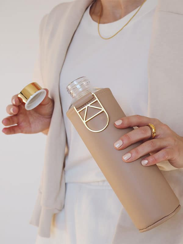 Gold lid and details of glass water bottle with beige colour cover - Sienna by EQUA